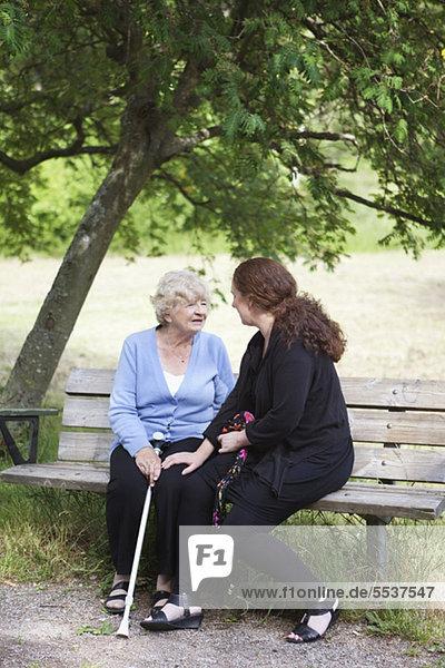 Großmutter und Enkelin sitzen zusammen auf der Parkbank.
