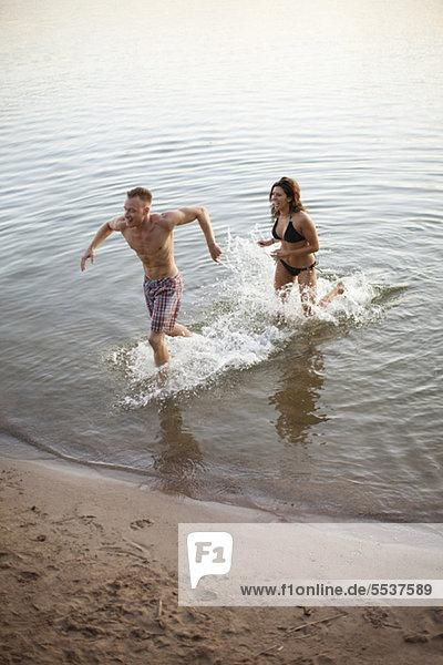 Heterosexuelles Paar  das durchs Wasser läuft