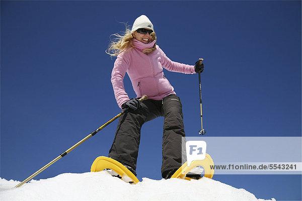 Junge Frau  etwa 25 Jahre  beim Schneeschuhfahren mit Stöcken in der Hand  im Schnee vor stahlblauem Himmel  Thüringer Wald  Thüringen  Deutschland  Europa