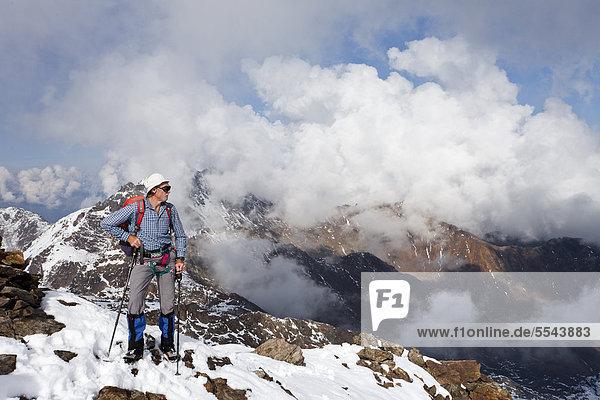 Wanderer auf der Lorcherspitz oberhalb des Grünsees  hinten Weißbrunnspitze und Zufrittspitze im Hochnebel  Südtirol  Italien  Europa Wanderer auf der Lorcherspitz oberhalb des Grünsees, hinten Weißbrunnspitze und Zufrittspitze im Hochnebel, Südtirol, Italien, Europa