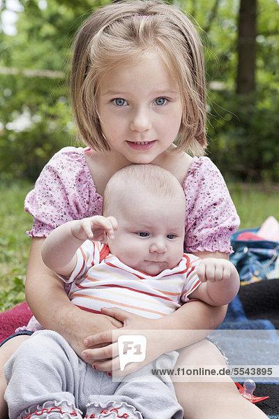 Vierjähriges Mädchen mit Baby im Arm