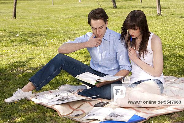 Junges Paar sitzt auf einer Decke mit Unterlagen
