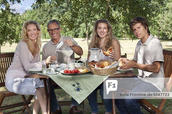Vierköpfige Familie beim Frühstück am Gartentisch