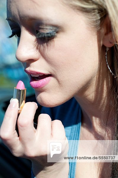 Portrait of a 31 year old blond woman putting lipstick on her lips