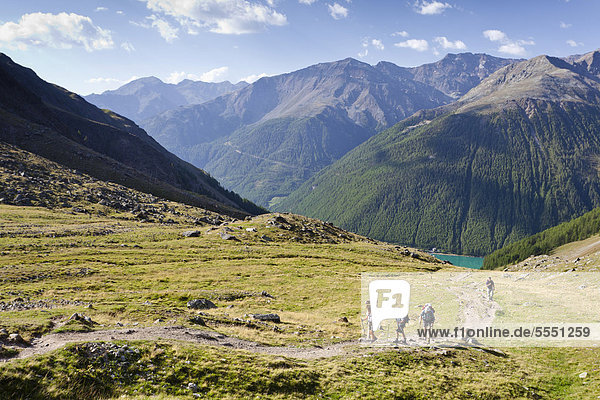 Hikers ascending to the Similaun Hut  Schnalstal Valley through Tisental Valley  with th Vernagt Reservoir below  Alto Adige  Italy  Europe