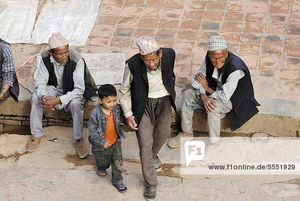 Männer mit traditioneller Kopfbedeckung und Junge auf dem Taumadhi-Platz  Bhaktapur  Kathmandu-Tal  Nepal  Asien