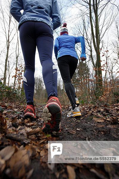 Zwei junge Frauen laufen im Winter im Wald  mit wind- und wasserdichter Funktionsbekleidung