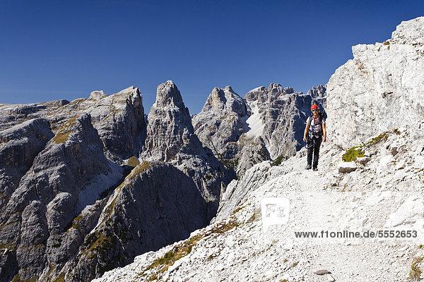 Wanderer im Alpinisteig am Einser  hinten die Dreischusterspitze  Sexten  Hochpustertal  Dolomiten  Südtirol  Italien  Europa Wanderer im Alpinisteig am Einser, hinten die Dreischusterspitze, Sexten, Hochpustertal, Dolomiten, Südtirol, Italien, Europa