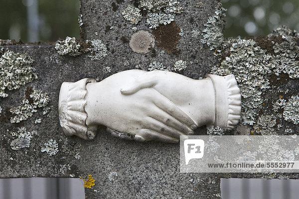 Sculptured handshake on a weathered grave stone  Mora  Dalarna  Sweden  Europe