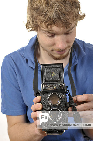 Young man taking a photograph with an analog 6x6 twin-lens TLR camera