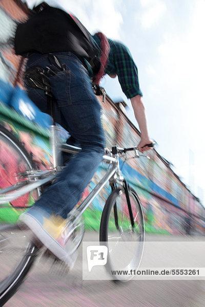 Mittlerer Erwachsener Radfahrer mit dem Fahrrad über die Brücke