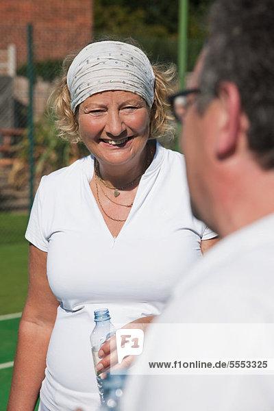 Leitende und ältere Erwachsene genießen Getränk am Tennisplatz
