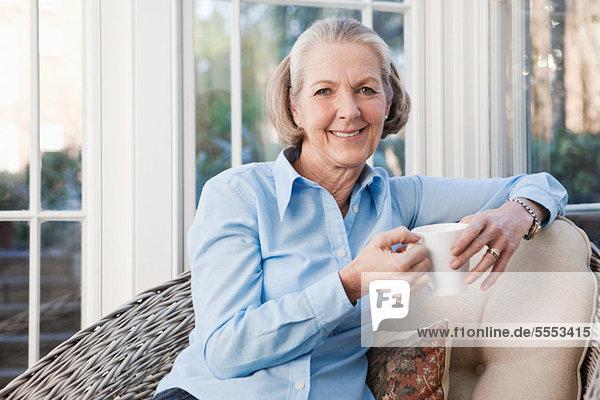 Seniorin entspannt mit heißem Getränk
