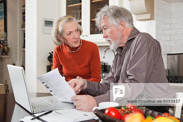Senior Paar sucht mit Rechnungen und Laptop besorgt