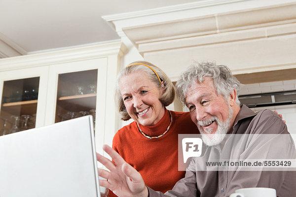 Seniorenpaar mit Webcam am Laptop