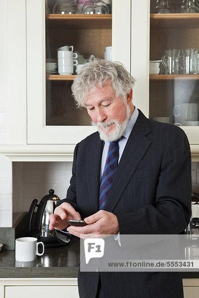 Senior Businessman in Küche mit smartphone