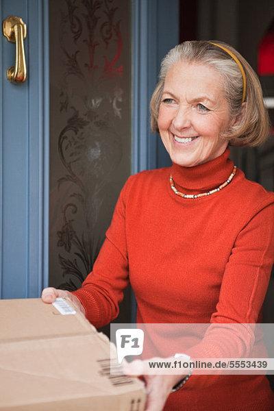 Seniorin erhält Paket vor der Haustür