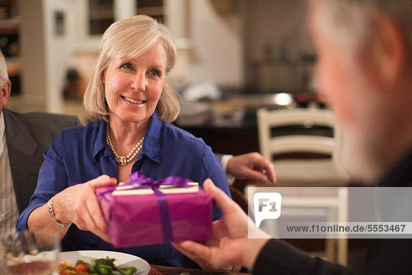 Reife Frau bei Abendessen Geschenk erhalten
