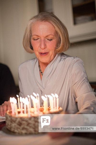 Senior Woman Ausblasen der Kerzen auf der Geburtstagstorte