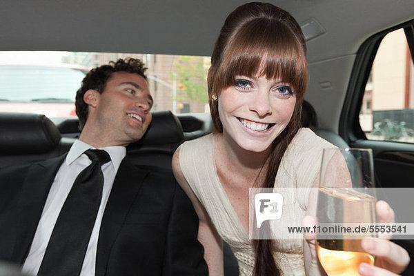 Brautpaar im Auto mit Champagner