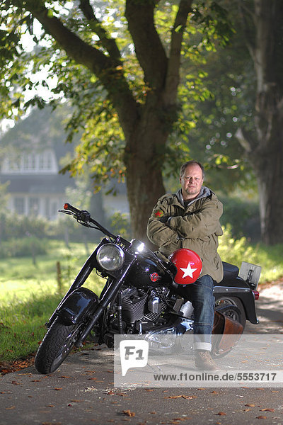 Mann sitzt auf einem Motorrad auf einer Landstraße