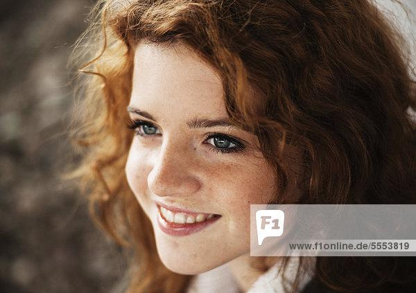 Lächelnde Teenagerin mit lockigen Haaren