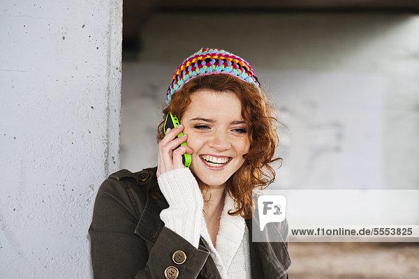 Teenagerin mit lockigen Haaren und Wollmütze telefoniert