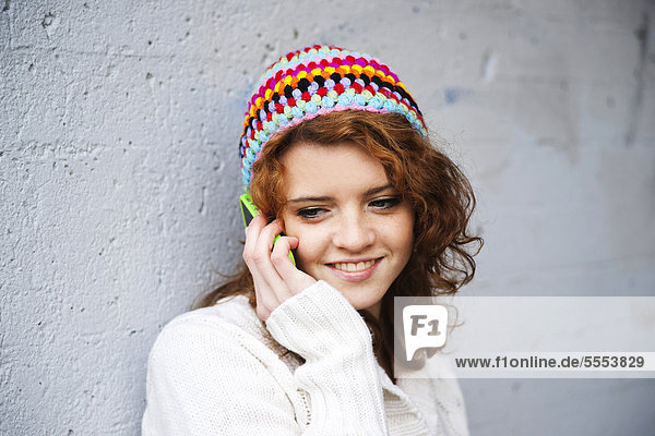 Teenager girl with curly hair wearing beanie on the phone