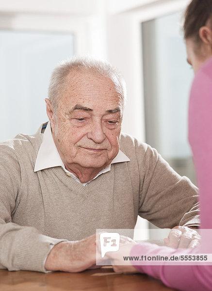 Junge Frau und Senior sitzen Hand in Hand am Tisch