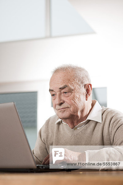Senior man using laptop at table