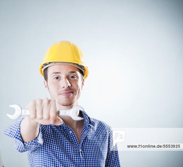 Young man wearing hard hat holding wrench  portrait
