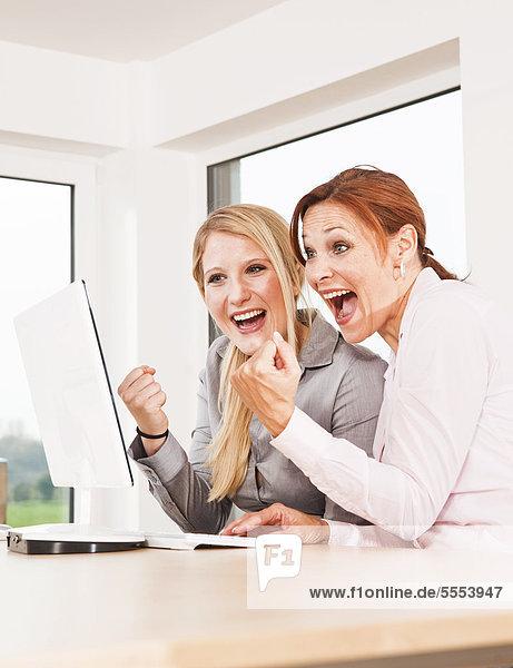 Zwei jubelnde Geschäftsfrauen am Schreibtisch