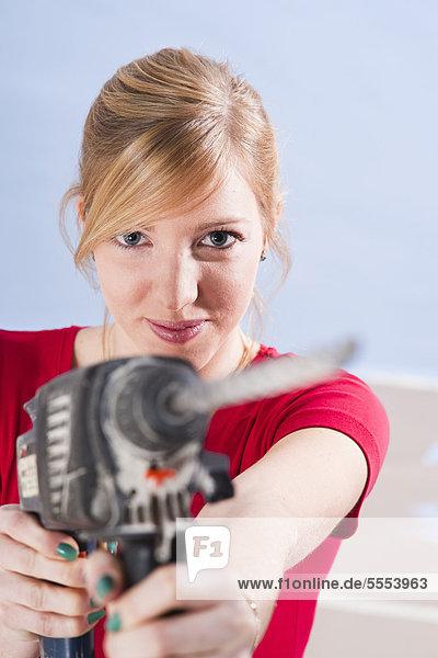 Junge Frau hält eine Bohrmaschine