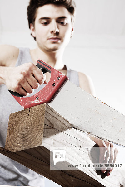 Young man sawing wooden block