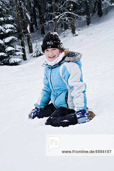 Mädchen im Schnee sitzend
