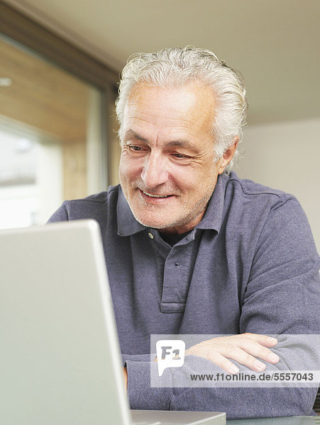 Senior man using laptop,  smiling