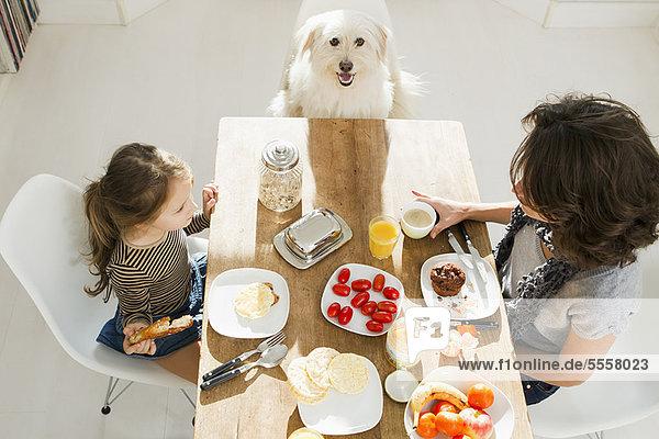 Mutter und Tochter bei Tisch mit Hund Mutter und Tochter bei Tisch mit Hund
