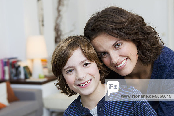Mother and son hugging in living room