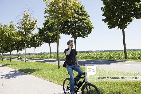 Mann im Gespräch auf dem Handy auf dem Fahrrad