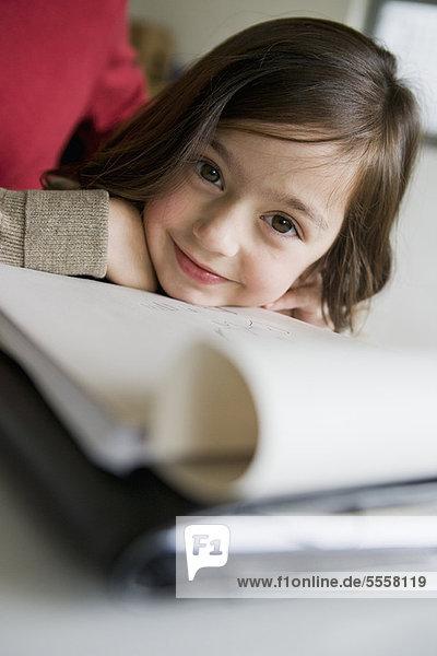 Smiling girl doing her homework at desk