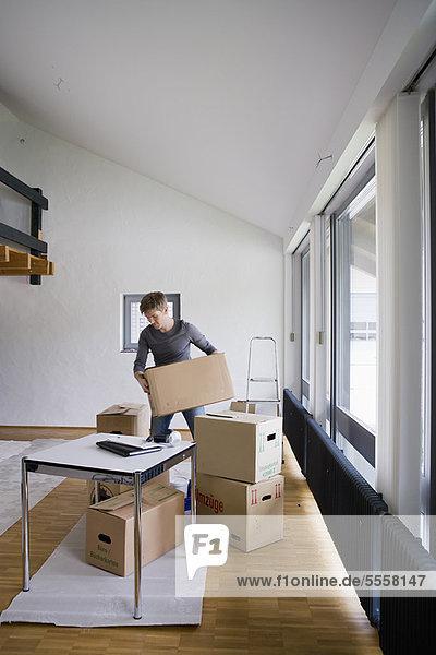 Mann stapelt Kartons im Haus