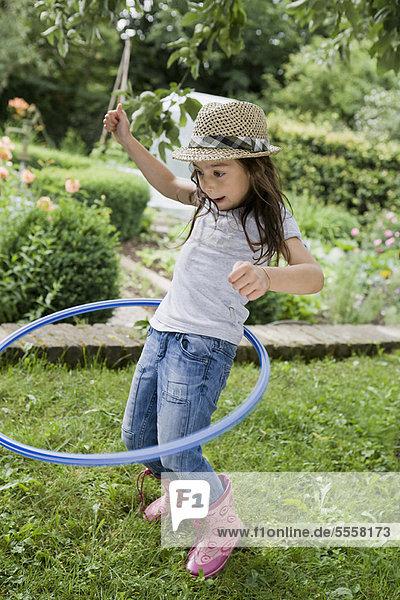 Mädchen spielt mit Hula Hoop im Hinterhof