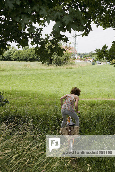 Fahrradfrau im hohen Gras