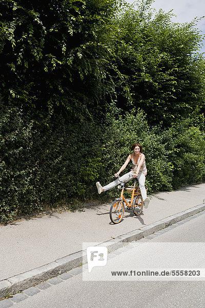 Frau beim Radfahren auf der Landstraße