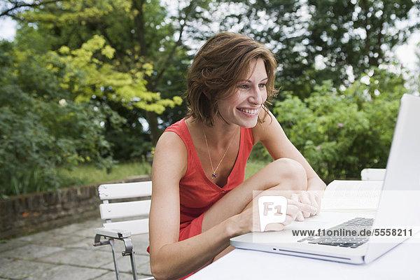 Smiling woman using laptop in backyard