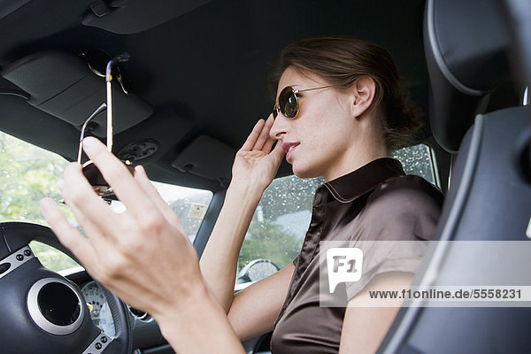 Frau beim Anprobieren der Sonnenbrille im Auto