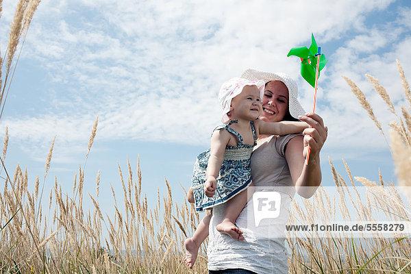 Frau hält Windrad für Tochter