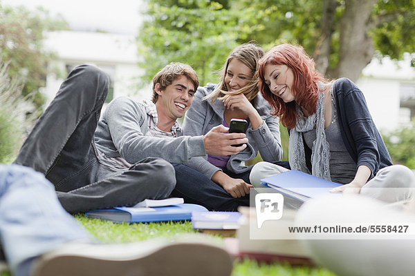 Studenten  die ihr Handy auf Rasen benutzen