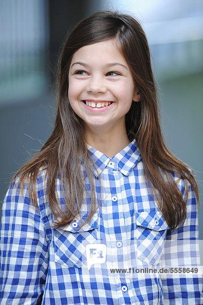 Lächelndes Mädchen mit kariertem Hemd