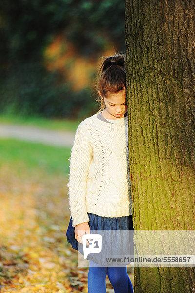 Mädchen lehnt an Baum im Park